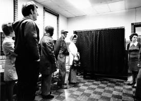 Election_day_4_November_1974_Fort_Wayne_IN_showing_voters_waiting_their_turn_at_the_North_Side_Park_Gymnasium_voting_booth_Voter_Vicky_Timinsky_is_shown_at_right (1)
